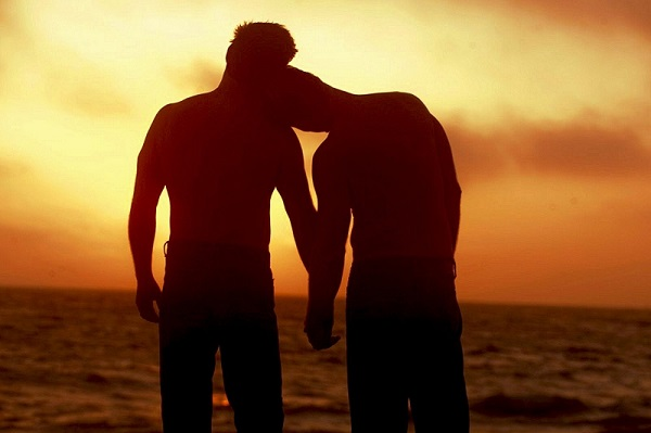 two-men-on-the-beach-at-sunset-holding-hands