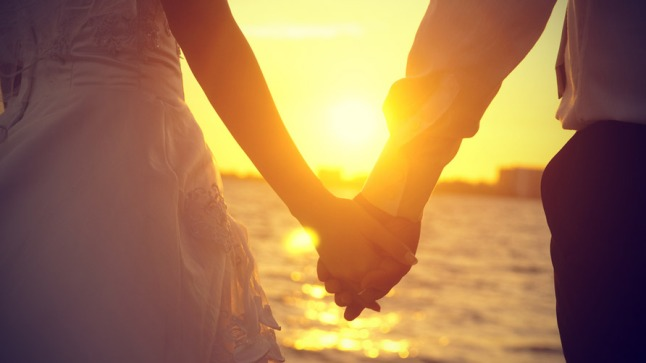 man-and-woman-holding-hands-in-sunset