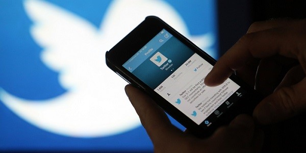 A user scrolls through a Twitter feed on the screen of an Apple Inc. iPhone 5 smartphone in this arranged photograph taken in London, U.K., on Friday, Oct. 4, 2013. Twitter Inc.'s initial public offering documents suggested a valuation of $12.8 billion for the microblogging service, underscoring the seven-year rise of a still unprofitable company that has helped revolutionize how people share information. Photographer: Chris Ratcliffe/Bloomberg via Getty Images
